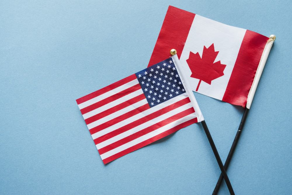 Canadian and American flags are on the blue surface