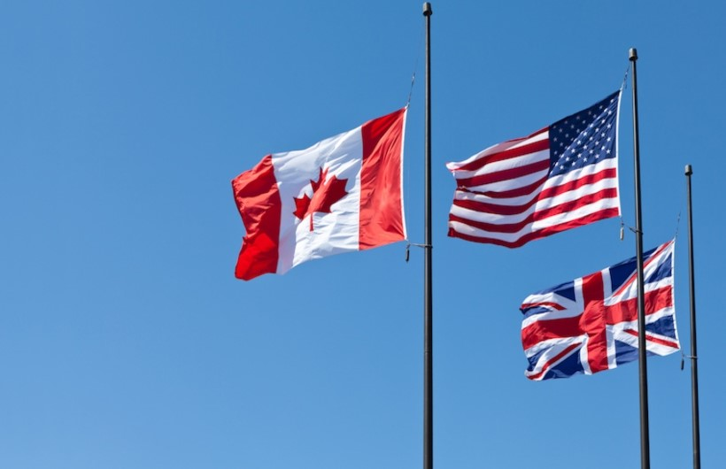 Flags of Canada, America and Britain at the background of the sky